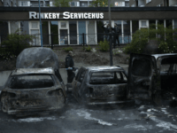 A police officers passes the scene of cars gutted by fire in the Stockholm suburb of Rinkeby after youths rioted in several different suburbs around Stockholm, Sweden for a fourth consecutive night on May 23, 2013. In the suburb of Husby, where the riots began on Sunday in response to …