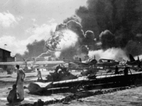 An explosion at the Naval Air Station, Ford Island, Pearl Harbour (Pearl Harbor) during the Japanese attack. Sailors stand amid wrecked watching as the USS Shaw explodes in the center background. The USS Nevada is also visible in the middle background, with her bow headed toward the left. (Photo by …