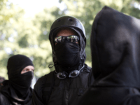 Antifa protesters wear bandanas over their face during a protest to oppose the right wing group 'The Patriot Prayer Movement,' that was having a rally in downtown Portland, Oregon on September 10, 2017. Several hundred protesters descended in to downtown Portland to oppose the right-wing group. / AFP PHOTO / …