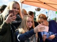 A girl (C) poses for a selfie photo with German Chancellor Angela Merkel (R) as she continued on the election campaign trail at a town fair in Stralsund on September 16, 2017, a week before Germans head to the polls. / AFP PHOTO / John MACDOUGALL (Photo credit should read …