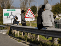 Migrants sit on the barriers along the ring road heading to the harbour of the French northern city of Calais, on November 2, 2017, next to a lorry parking lot. In Calais, local associations put the number of migrants sleeping rough around the town at around 600-700 and they have …