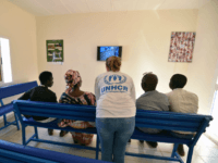 A UNHCR representative (C) speaks with refugees as they watch television in a UNHCR building in Niamey, on November 17, 2017, after being evacuated from Libya and ahead of interviews by protection officers of the French Office of Protection Refugees and Stateless Persons (OFPRA). France will be the first to …