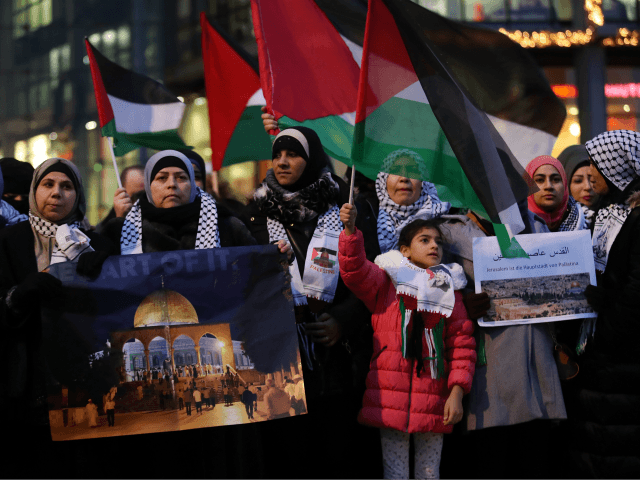 BERLIN, GERMANY - DECEMBER 12: Arabic-speaking protesters, including a woman holding a photograph of the Dome of the Rock in Jerusalem, attend a gathering to protest against the recent announcemment by U.S. President Donald Trump to recognize Jerusalem as the capital of Israel on December 12, 2017 in Berlin, Germany. The protesters waved Palestinian flags and chanted 'Allahu Akbar.' Some also chanted 'Fuck you, Donald Trump.' Today's protest was the fourth in as many days and follows a Sunday protest that drew several thousand demonstators. (Photo by Sean Gallup/Getty Images)
