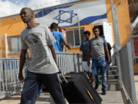 African illegal migrants carry their belongings following their release from the Holot Detention Centre in Israel's Negev desert, on August 25, 2015. Israel began releasing hundreds of African migrants from the detention centre after a court order, but the asylum-seekers were barred from entering two cities. A recent court decision ordered Israel to release the illegal migrants held for more than a year at a detention centre in the Negev desert, a ruling affecting 1,178 of the asylum-seekers. AFP PHOTO/MENAHEM KAHANA (Photo credit should read MENAHEM KAHANA/AFP/Getty Images)
