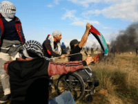 A picture taken on December 15, 2017 shows wheelchair-bound Palestinian demonstrator Ibrahim Abu Thurayeh waving a Palestinian flag during a protest along the Gaza-Israel border, as clashes with Israeli security forces against Washington's recognition of Jerusalem as Israel's capital intensified. The 29-year-old Abu Thurayeh, who had previously lost both his legs, was shot on December 15 along the border east of Gaza City in the north of the Palestinian enclave, the Palestinian health ministry said, shortly after another man was killed in similar circumstances. / AFP PHOTO / MOHAMMED ABED (Photo credit should read MOHAMMED ABED/AFP/Getty Images)