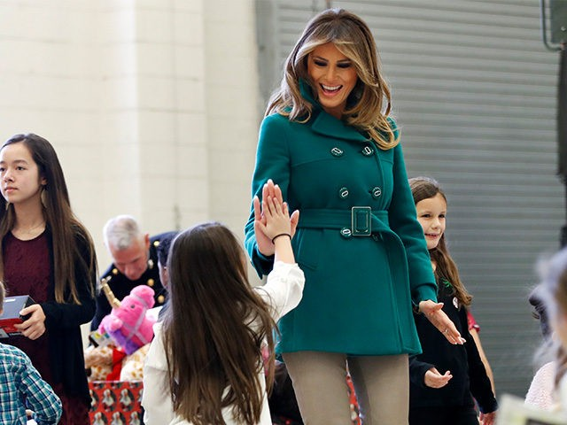 "First lady Melania Trump high fives the daughter of a military family, Wednesday, Dec. 13, 2017, while sorting toys during a ""Toys for Tots"" event at Joint Base Anacostia-Bolling in Washington. (AP Photo/Jacquelyn Martin)"