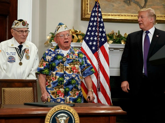 Alexander Horanzy, left, and President Donald Trump listen to Mickey Ganitch sing a song about Pearl Harbor during an event with survivors of the attack, in the Roosevelt Room of the White House, Thursday, Dec. 7, 2017, in Washington. (AP Photo/Evan Vucci)