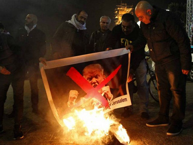 TOPSHOT - Palestinian protesters burn pictures of US President Donald Trump at the manger square in Bethlehem on December 5, 2017. US President Donald Trump told Palestinian leader Mahmud Abbas in a phone call that he intends to move the US embassy from Tel Aviv to Jerusalem, Abbas's office said. …