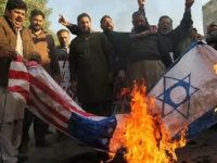 Protester burn US and Israeli flags during a protest in Multan on December 7, 2017, following US President Donald Trump's decision to officially recognise Jerusalem. / AFP PHOTO / - (Photo credit should read -/AFP/Getty Images)