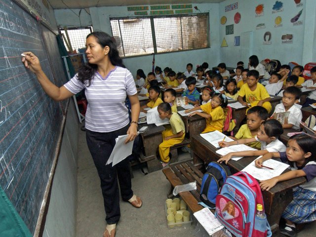 Manila, PHILIPPINES: Teacher Leonora Jusay give a lesson to her 59 students of a Grade 2 class, packed in small classroom that was a former toilet of the government-run Commonwealth Elementary School in Quezon city, suburban Manila, 07 July 2006. The dire situation in this overcrowded public school has become …