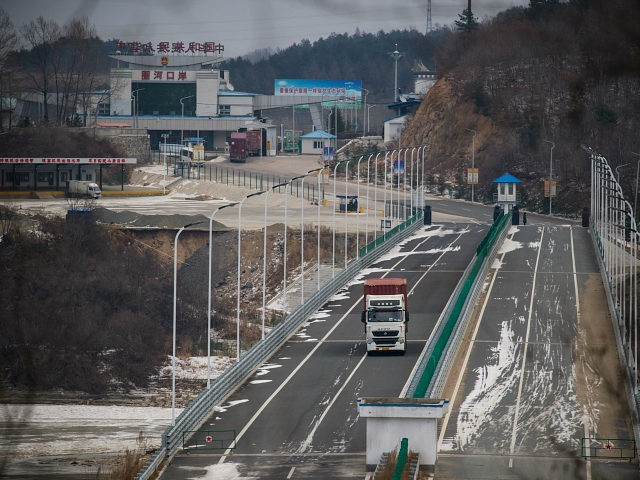 In a photo taken on November 21, 2017, a truck entering the Rason Special Economic Zone makes its way across a bridge over the Tumen river marking the border between North Korea (bottom) and China (top). At the northeastern tip of North Korea, where the isolated, nuclear-armed country meets its giant neighbours China and Russia, United Nations sanctions on the regime over its weapons programmes are having an impact. And with the North facing further sanctions following its ICBM missile test on November 29, things are unlikely to get any easier for traders involved with the remote region's Rason Special Economic Zone (SEZ). / AFP PHOTO / Ed JONES / TO GO WITH NKorea-China-trade-sanction-diplomacy, FOCUS by Sebastien BERGER (Photo credit should read ED JONES/AFP/Getty Images)
