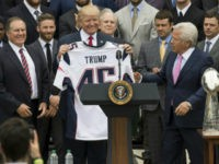 US President Donald Trump holds a jersey given to him by New England Patriots owner Robert Kraft (R) and head coach Bill Belichick (L) alongside members of the team during a ceremony honoring them as 2017 Super Bowl Champions on the South Lawn of the White House in Washington, DC, …