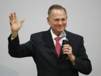 Roy Moore with hand raised and smile