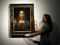 An employee poses with Leonardo da Vinci's 'Salvator Mundi' on display at Christie's auction rooms, in London, Tuesday, Oct. 24, 2017. The painting will be sold in the Post-War and Contemporary Art Evening Auction taking place on Nov.15 at Christie's New York. The estimate is in the region of 100 …