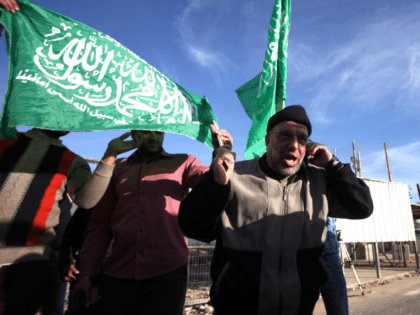 Sheikh Hassan Yousef (C), a prominent leader of the Hamas Islamic movement, holds the party's flag and talks on a phone following his release on January 19, 2014 after spending 28 months in Israel's Ofer prison, near the West Bank city of Ramallah. Yousef, who is also a member of the Ramallah-based Palestinian Legislative Council, told reporters after being released that he would work with Hamas rivals 'Fatah and other Palestinian factions to achieve reconciliation.' AFP PHOTO / ABBAS MOMANI (Photo credit should read ABBAS MOMANI/AFP/Getty Images)