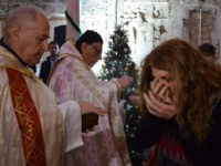 An Iraqi receives the Eucharist during a Christmas mass at the Saint Paul's church on December 24, 2017 in the country's second city Mosul. Hymns filled a church as worshippers celebrated Christmas for the first time in four years after the end of jihadist rule. Tens of thousands of Christians …