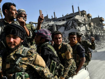Kurdish fighters of the Syrian Democratic Forces (SDF) ride in the back of a truck passing damaged buildings in Raqa on October 20, 2017, after a Kurdish-led force expelled the Islamic State group from the northern Syrian city. For three years, Raqa saw some of IS's worst abuses and grew …