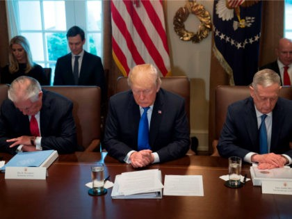 US President Donald Trump bows his head during a prayer, alongside Secretary of State Rex Tillerson (L) and Secretary of Defense Jim Mattis (R) during a Cabinet Meeting in the Cabinet Room at the White House in Washington, DC, December 20, 2017. / AFP PHOTO / SAUL LOEB (Photo credit …
