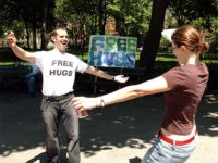 NEW YORK - MAY 16: Jayson Littman spreads his arms as he prepares to hug a woman May 16, 2004 in Washington Square Park In New York City. For about the last month Jayson, a financial analyst, has been offering free hugs on Sunday from 1pm to 4pm. (Photo by Stephen Chernin/Getty Images)