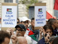 A Pro-Palestinian demonstrator carries placards reading 'Keep calm and boycott Israel' on the Republique square in Paris, ahead of a banned demonstration against Israel's military operation in Gaza and in support of the Palestinian people, on July 26, 2014. French authorities banned on July 26, 2014 a new pro-Palestinian demonstration over concerns it could turn violent as previous rallies have, but demonstrators may ignore the ban as they did last weekend. US Secretary of State John Kerry and other top diplomats from Europe and the Middle East began talks in Paris on July 26 to press efforts for a long-term ceasefire between Israel and Hamas. AFP PHOTO / KENZO TRIBOUILLARD (Photo credit should read KENZO TRIBOUILLARD/AFP/Getty Images)
