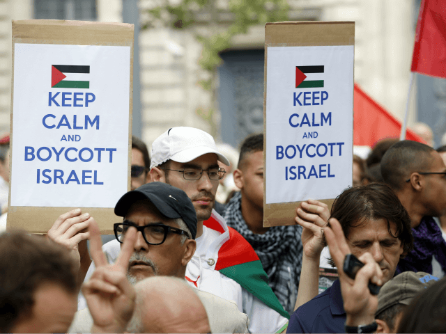 A Pro-Palestinian demonstrator carries placards reading 'Keep calm and boycott Israel' on the Republique square in Paris, ahead of a banned demonstration against Israel's military operation in Gaza and in support of the Palestinian people, on July 26, 2014. French authorities banned on July 26, 2014 a new pro-Palestinian demonstration …