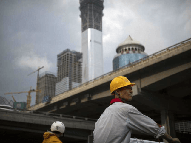 FILE - In this Aug. 16, 2017, file photo, a construction worker waits to cross an intersection near buildings under construction in the central business district of Beijing. The World Inequality Report 2018 released Friday, Dec. 15, 2017, is based on a massive collection of data compiled by an international …