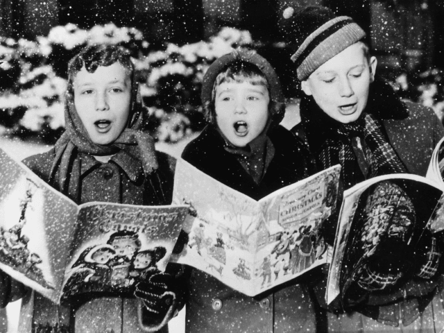 1957: Three young carol singers give their rendering of a Christmas song in the falling snow. (Photo by Keystone/Getty Images)