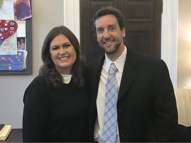 Clay Travis and Sarah Huckabee Sanders pose together for a picture in the White House on December 5, 2017.