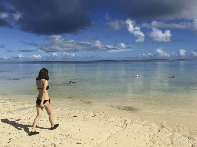 A tourist enters the waters of Tumon Bay on the island of Guam, Tuesday, Aug. 15, 2017. The nuclear conflict with North Korea that has made Guam the target of a threatened attack has led to new calls to change the government of the Pacific island whose inhabitants are American citizens but have no say in electing the president or the use of military force. (AP Photo/Tassanee Vejpongsa)