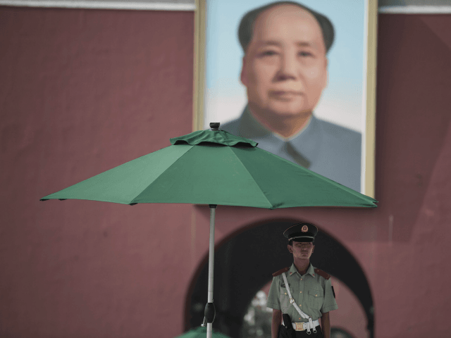 A Chinese paramilitary guard stands in front of a portrait of late communist leader Mao Zedong at the Forbidden City in Beijing on July 31, 2017, on the eve of the 90th founding anniversary of the People's Liberation Army (PLA). The PLA, originally called the Chinese Workers' and Peasants' Red Army, was founded in 1927 when Communist soldiers seized the southern town of Nanchang from Nationalist Party ('Kuomintang') armies in what is known today as the Nanchang uprising. / AFP PHOTO / FRED DUFOUR (Photo credit should read FRED DUFOUR/AFP/Getty Images)