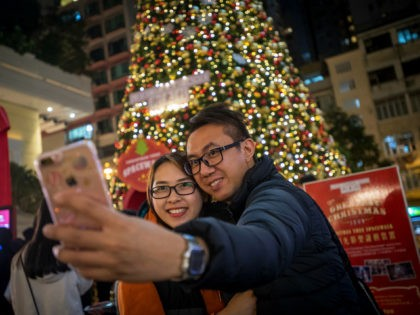 People take a selfie photograph with an Apple Inc. iPhone in front of an illuminated Christmas tree in Hong Kong, China, on Saturday, Dec. 9, 2017. With more Chinese tourists likely to travel to Hong Kong next year as the yuan strengthens against the Hong Kong dollar, retailers are poised to …