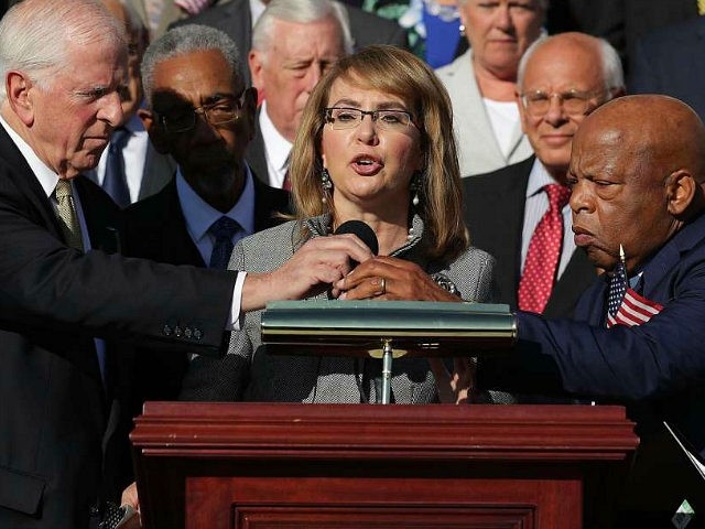 WASHINGTON, DC - OCTOBER 04: Rep. Mike Thompson (D-CA) (L) and Rep. John Lewis (D-GA) adjust the microphone for former Congresswoman and gun violence victim Gabby Giffords (C) as she addresses a rally with fellow Democrats on the East Front steps of the U.S. House of Representatives October 4, 2017 in Washington, DC. The Democratic members of Congress held the rally to honor the victims of the mass shooting in Las Vegas and to demand passage of the bipartisan King-Thompson legislation to strengthen background checks and establishing a bipartisan Select Committee on Gun Violence. (Photo by Chip Somodevilla/Getty Images)