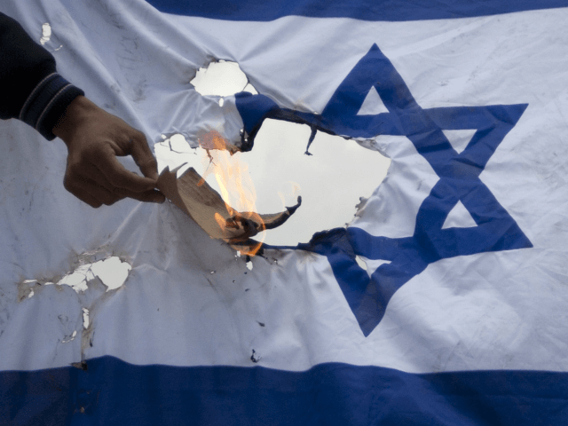 A Palestinian protester burns an Israeli flag after the funeral of Palestinian Milad Said Ayyash, 17, who died of wounds sustained in yesterday's protests in east Jerusalem, Saturday, May 14, 2011.(AP Photo/Sebastian Scheiner)