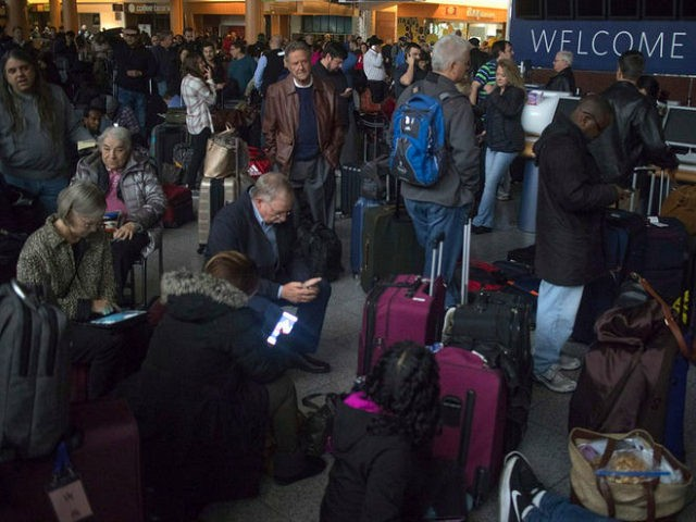 Passengers wait in a dark terminal at Hartsfield-Jackson International Airport, Sunday, Dec. 17, 2017, in Atlanta. A sudden power outage at the Hartsfield-Jackson Atlanta International Airport on Sunday grounded scores of flights and passengers during one of the busiest travel times of the year. (Steve Schaefer/AP)