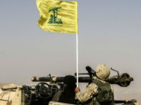 A picture taken on August 2, 2017 during a tour guided by the Lebanese Shiite Hezbollah movement shows one of the group's fighters flying the group's flag as he sits in a four-wheel drive vehicle carrying a recoilless rifle, in a mountainous area around the Syrian town of Flita near …