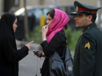 TEHRAN, IRAN - APRIL 22: An Iranian policewoman (L) warns a woman about her clothing and hair during a crackdown to enforce Islamic dress code on April 22, 2007 in Tehran, Iran. Police issued warnings and conducted arrests during an annual pre-summer crackdown, which was given greater prominence this year, …