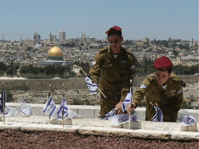 Israeli soldiers place flags on the graves of Jews killed in the battle for Jerusalem during Israel's 1948 War of Independence, on the eve of Memorial Day, Yom Hazikaron, at a small military cemetery on the Mount of Olives on May 6, 2008 in Jerusalem. Israel will remember its 22,437 fallen troops during tomorrow's annual Memorial Day commemorations, which falls the day before Israel's annual Independence Day celebrations. This year marks the 60th anniversary of the Proclamation of the State of Israel in 1948. The Dome of the Rock on the compound known to Muslims as al-Haram al-Sharif, and to Jews as Temple Mount, is seen in the background. (Photo by Brian Hendler/Getty Images)