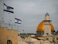 Israeli flags fly near the Dome of the Rock in the Al-Aqsa mosque compound on December 5, 2017. The EU's diplomatic chief Federica Mogherini said that the status of Jerusalem must be resolved 'through negotiations', as US President Donald Trump mulls recognising the city as the capital of Israel. / AFP PHOTO / THOMAS COEX (Photo credit should read THOMAS COEX/AFP/Getty Images)