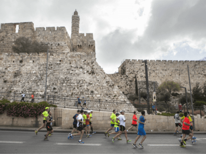 Runners pass the Tower of David as they participate in the annual marathon in Jerusalem, Friday, March 18, 2016. The Jerusalem municipality says a Kenyan runner, 25-year-old Kipkogey Shadrack, won this year's marathon in the holy city with a time of 2:16:33. (AP Photo/Dan Balilty)