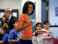 ALEXANDRIA, VA - JANUARY 25: U.S. first lady Michelle Obama joins students at the food line to pick up lunch items at the cafeteria of Parklawn Elementary School January 25, 2012 in Alexandria, Virginia. The first lady, accompanied by Agriculture Secretary Tom Vilsack and celebrity cook Rachael Ray, visited the …