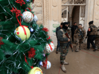 Iraqi security forces stand guard as Christians attend a Christmas Eve service at the Mar Shimoni church in the town of Bartalla near Mosul on December 24, 2016 for the first time since its recapture from Islamic State (IS) jihadists. IS seized Bartalla and swathes of other territory north and west of Baghdad in the summer of 2014, leaving Christians with the grim choices of conversion, paying a tax, fleeing or death. The town was recaptured as part of the massive military operation to retake Mosul, the last IS-held Iraqi city, which was launched on October 17. / AFP / SAFIN HAMED (Photo credit should read SAFIN HAMED/AFP/Getty Images)