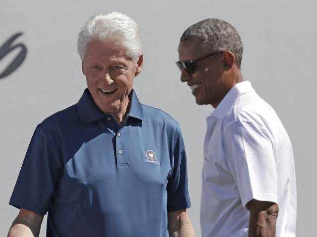 Former Presidents Barack Obama, right, and Bill Clinton greet U.S. team members before the first round of the Presidents Cup at Liberty National Golf Club in Jersey City, N.J., Thursday, Sept. 28, 2017. (AP Photo/Julio Cortez)