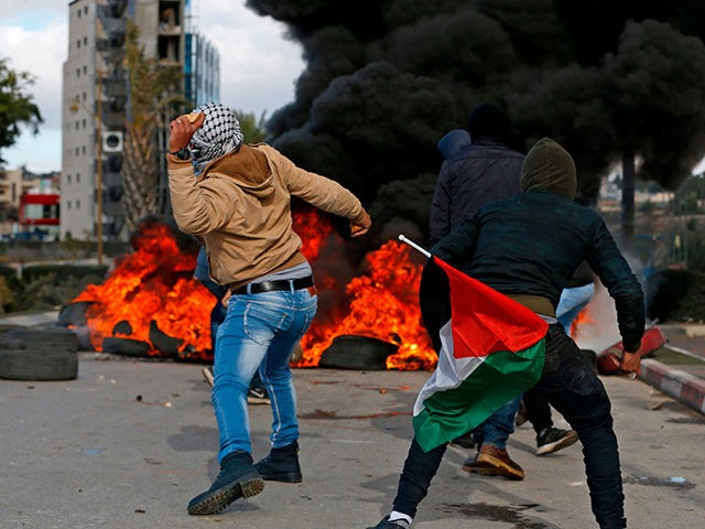 Palestinian demonstrators holding a national flag throw stones towards Israeli troops during clashes that followed protests against a decision by US President Donald Trump to recognise Jerusalem as the capital of Israel, in the West Bank city of Ramallah on December 7, 2017. / AFP PHOTO / ABBAS MOMANI (Photo …