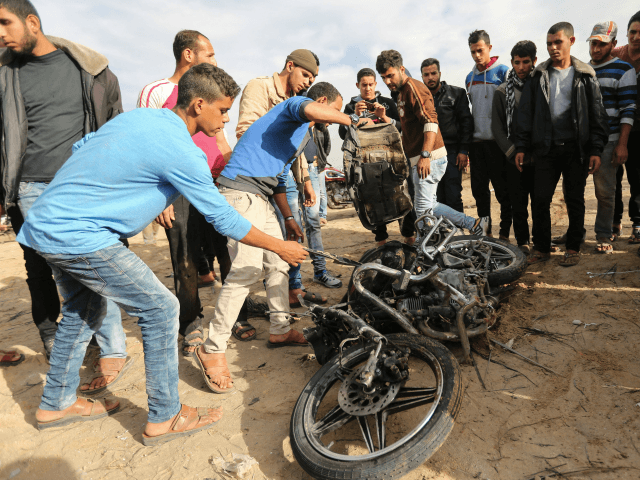 Palestinians inspect the damaged remains of a motorcycle, that was reportedly hit by an Israeli strike according to the Palestinian health ministry spokesman, in Beit Lahia in the northern Gaza Strip on December 12, 2017. Two Palestinians were killed in the Gaza Strip with authorities in the Hamas-run territory blaming …