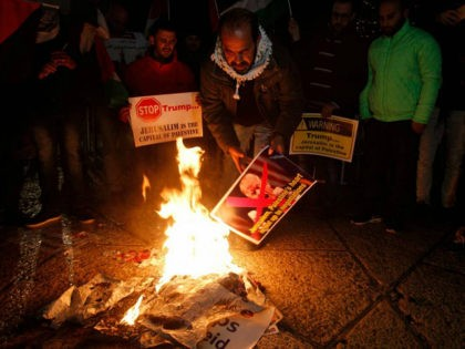 Palestinian demonstrators burn posters of the US president in Bethlehem's Manger Square in protest to him declaring Jerusalem as Israel's capital on December 6, 2017. Abbas said the United States can no longer play the role of peace broker after Donald Trump's decision on Wednesday to recognise Jerusalem as Israel's capital. / AFP PHOTO / Musa AL SHAER (Photo credit should read MUSA AL SHAER/AFP/Getty Images)