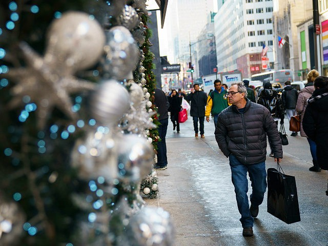 NEW YORK, NY - DECEMBER 18: A man carrying a shopping bag walks past holiday decorations along Fifth Avenue in Midtown Manhattan, December 18, 2017 in New York City. The city is decked out in holiday spirit with Christmas one week away from today. (Photo by Drew Angerer/Getty Images)