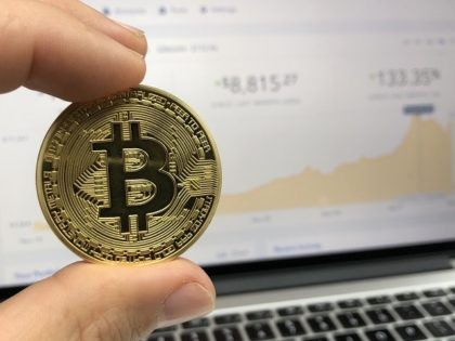 Bitcoin held in front of a computer screen showing a price chart on Coinbase.