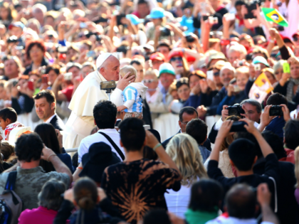 VATICAN CITY, VATICAN - OCTOBER 08: Pope Francis kisses a child as he arrives in St. Peter's square for his weekly public audience on October 8, 2014 in Vatican City, Vatican. Speaking to the crowds gathered in St. Peter's Square for the weekly General Audience Pope Francis appealed for Christian …
