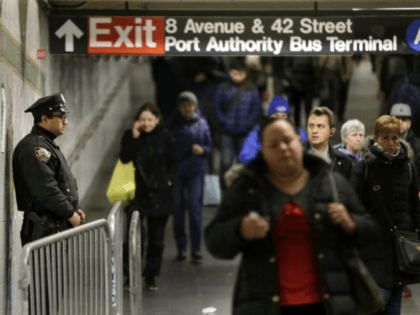 A police officer stands in the passageway connecting New York City's Port Authority bus terminal and the Times Square subway station Tuesday, Dec. 12, 2017, near the site of Monday's explosion. Commuters returning to New York City's subway system on Tuesday were met with heightened security a day after a …