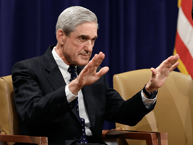 Outgoing FBI Director Robert Mueller (L) is applauded by Deputy Attorny General James Cole (C) and U.S. Attorney General Eric Holder during Mueller's farewell ceremony at the Department of Justice August 1, 2013 in Washington, DC. Mueller has served as the Director of the FBI since 2001. (Photo by Win …